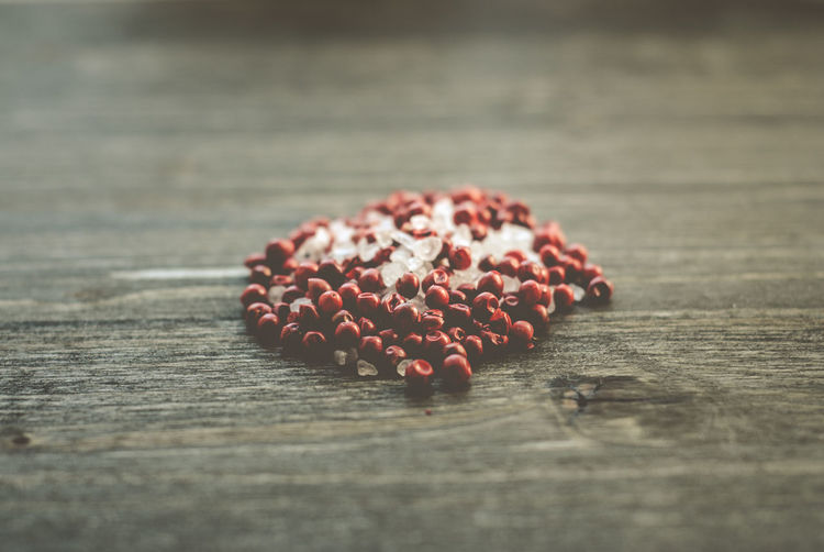Close-up of pink peppercorns and rock salt on table