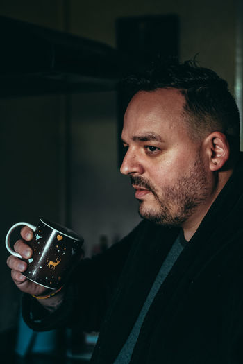Portrait of mid adult man holding cup of coffee