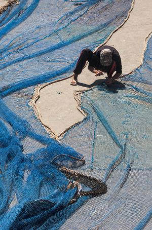 Man repairing blue fisher nets on the ground Crouching Fishing Net Repairs Sewing Sunny Blue Cowering Daylight Fisherman Fishermen Fishernet Sunlight View From Above