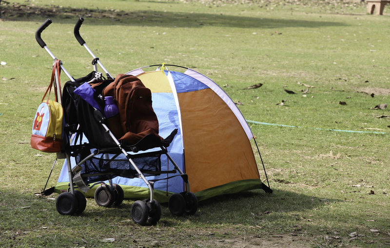 A baby stroller / carrier with some bags on it (including a purple water bottle) and a small multi colored kids tent right next to it, pitched on the grass. In the background is a garden hose pipe and some dry leaves. Baby Bag Baby Stroller Backpack Colorful Tent Garden Outdoors Small Tent Stroller Tent Tent In Garden