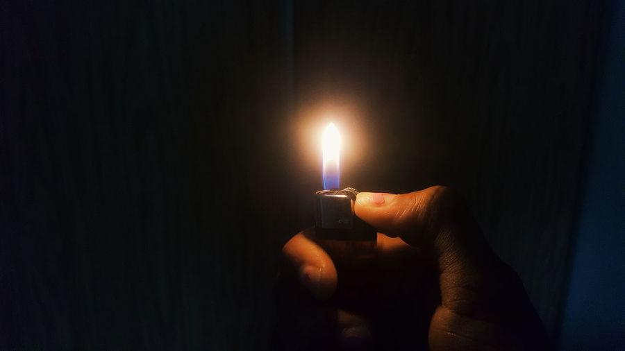 Holding cigarette lighter with flame over black background