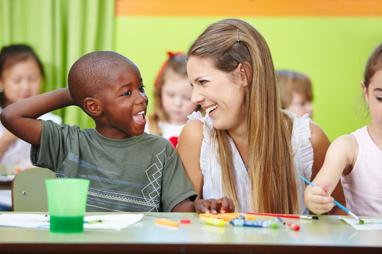 View of smiling teacher with kids in classroom
