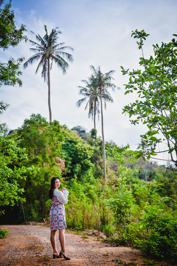 Rear view of woman walking on palm trees