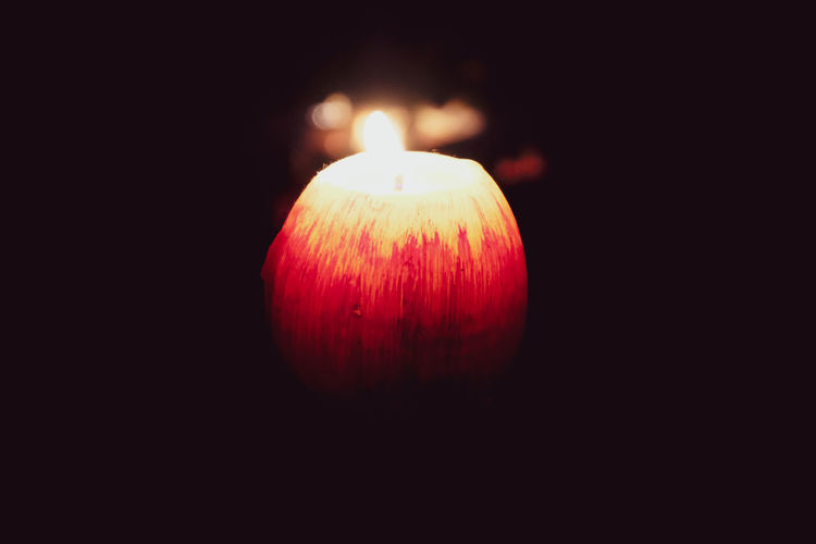 Close-up of lit candle against black background