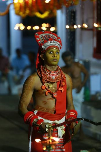 Man in traditional clothing holding weapons during theyyam