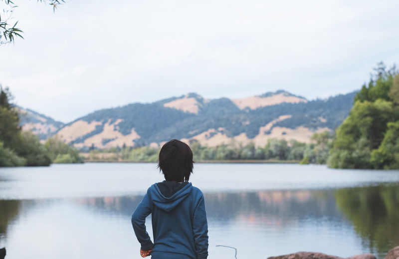 Rear View Of Child Standing Against Lake