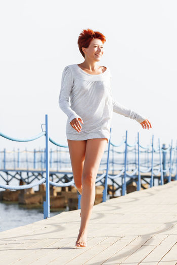 Wide smiling young woman with red short hair cut running on wooden pier. happiness, power of youth.