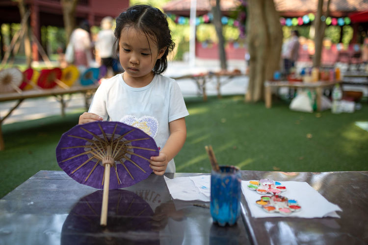 Cute girl painting umbrella in park