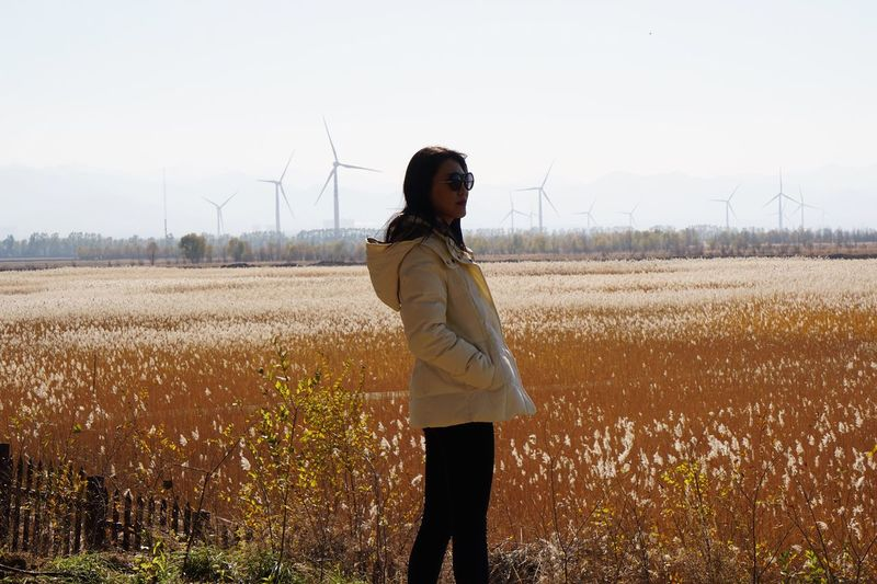 Fuel And Power Generation Environmental Conservation Alternative Energy One Person Only Women Field Wind Turbine Wind Power One Woman Only Standing Sustainable Lifestyle Adults Only Rural Scene Agriculture Long Hair Renewable Energy People Sustainable Resources Environmental Issues Adult Postcode Postcards