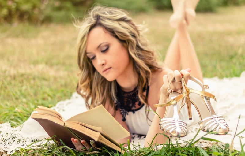 Portrait of young woman with book on field