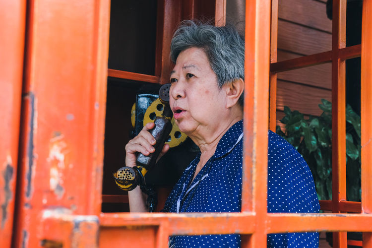 Senior woman talking on phone in telephone booth