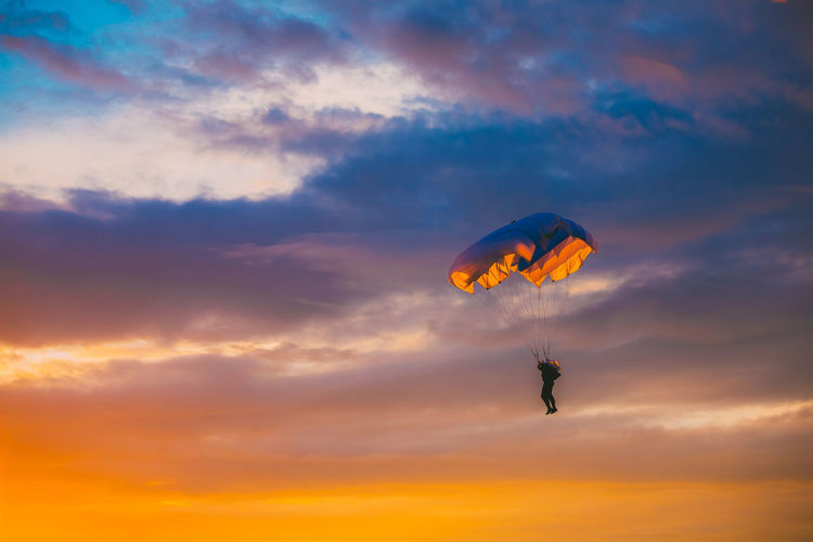 Low angle view of silhouette person paragliding against orange sky