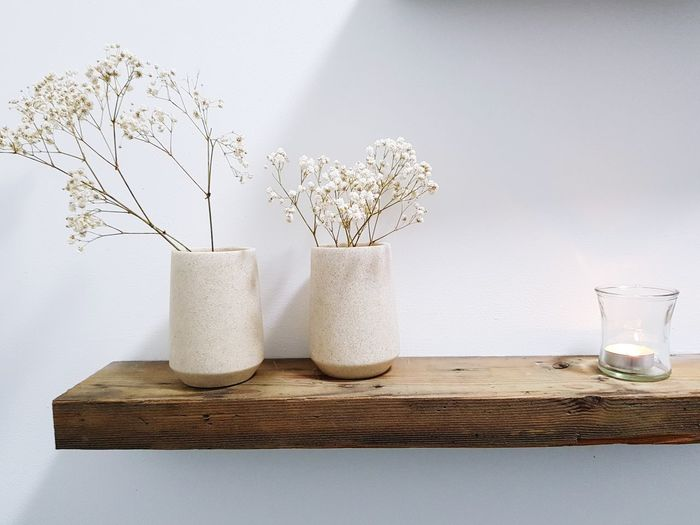 Close-Up Of Flowers In Vases On Shelf