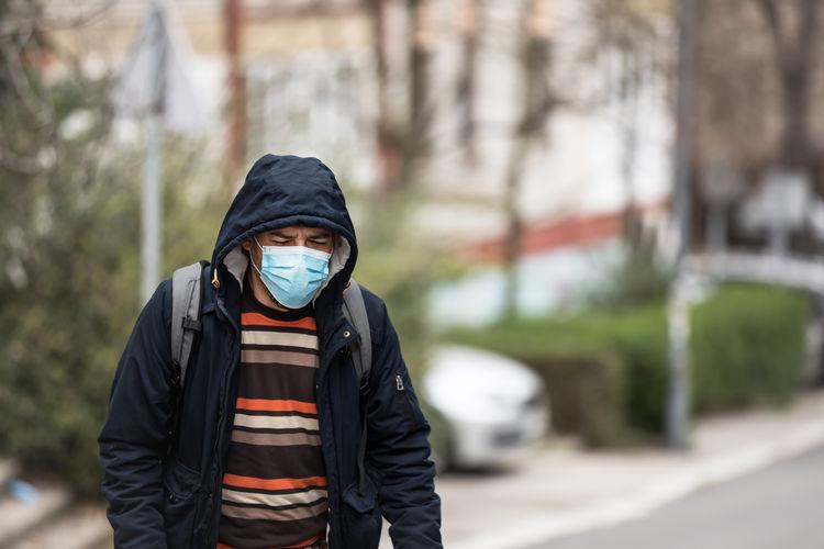 Man wearing mask and hood walking in city