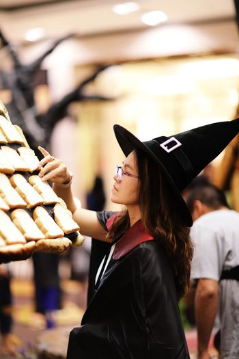 Side view of woman in witch costume arranging bread on house