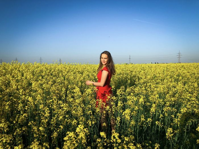 Woman in red dress in a field of canola flowers