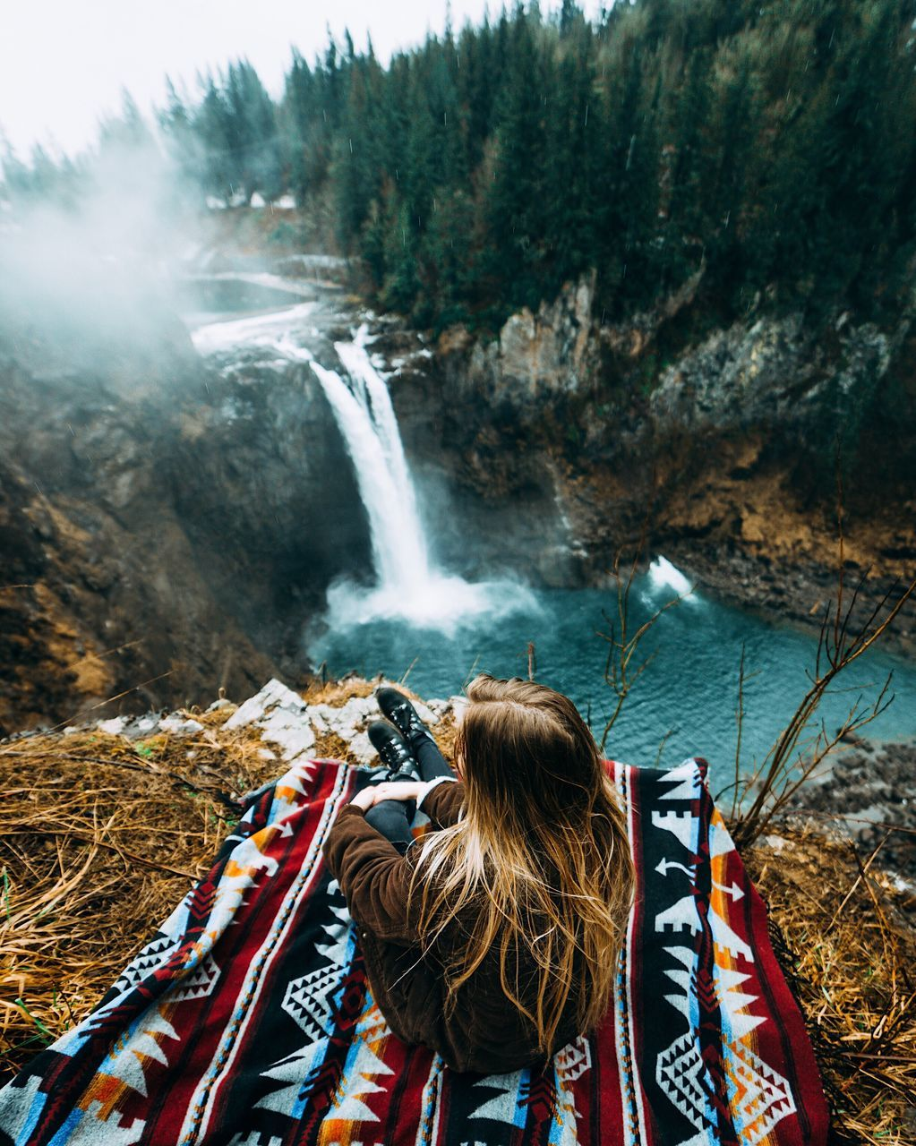 High Angle View Of Woman Relaxing On Mountain By Waterfall