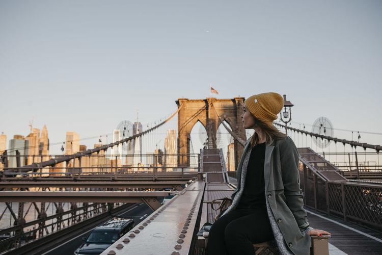 Woman standing on footbridge against clear sky