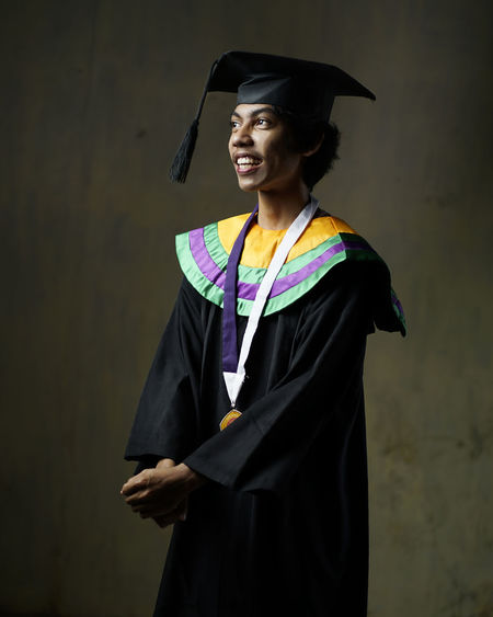Smiling man in graduation gown standing against wall