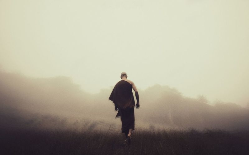 Rear view of monk wearing traditional clothing walking on field during foggy weather