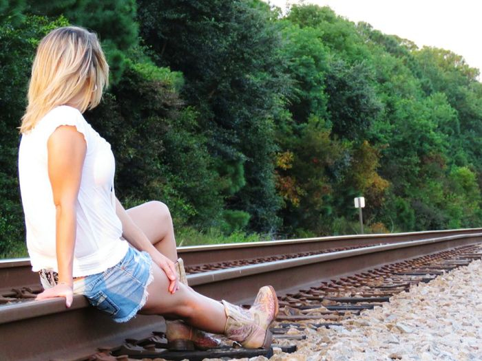Rear view of woman sitting on railroad track against trees