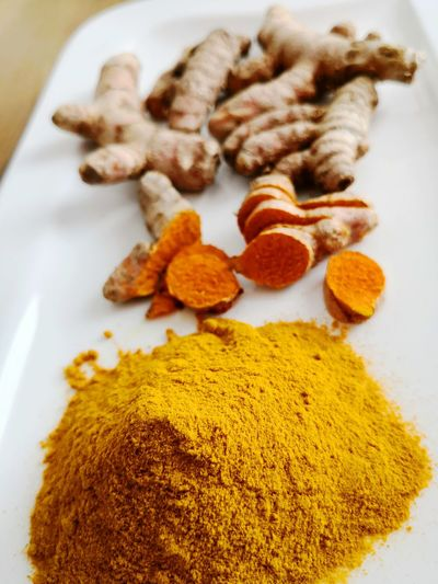 Curcuma turmeric powder and roots on white plate background Yellow Dyeing Turmeric Powder Turmericroot Turmeric Root Curcumin Curcuma Longa Curcuma Root Curcuma Alismatifolia Curcuma Longa Superfood Healthy Eating Stimulating Digestive System Close-up Turmeric  Ground - Culinary Curry Indian Food Ginger Black Peppercorn