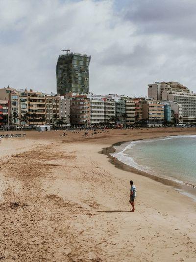 Man on beach against buildings in city