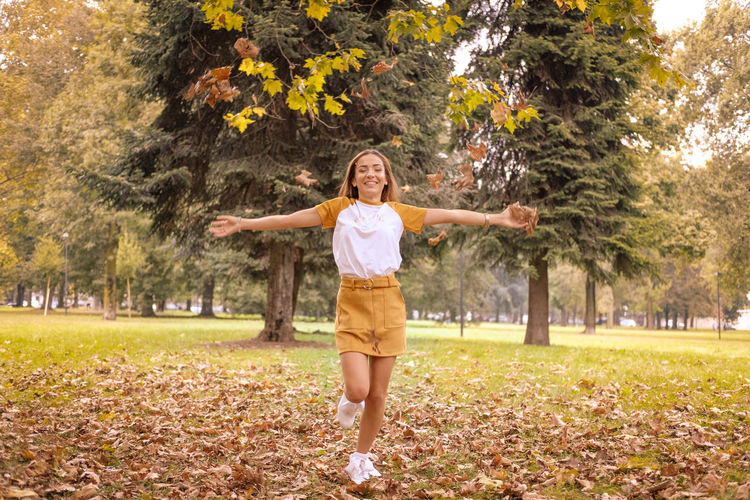 Young girl celebrating the arrival of autumn with open arms Arms Outstretched Arms Raised Body Part Change Day Emotion Front View Full Length Hair Hairstyle Happiness Human Arm Human Body Part Human Limb Leaf Limb Nature One Person Outdoors Plant Plant Part Smiling Standing Tree