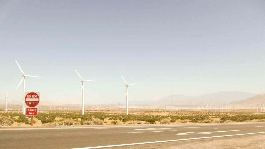 Windmills on road against sky