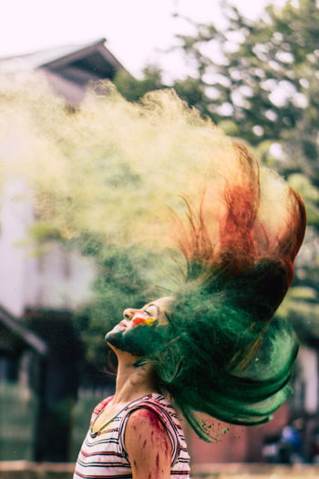 Woman splashing powder paint with hair against tree