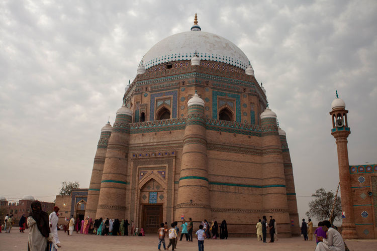 Group of people in front of historical tomb of  shahrukne alam multan against cloudy sky