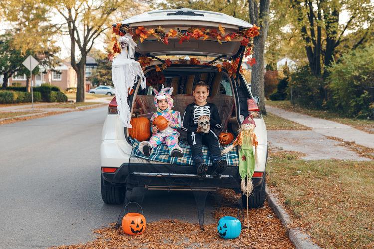 Cute kids wearing costume sitting in car trunk