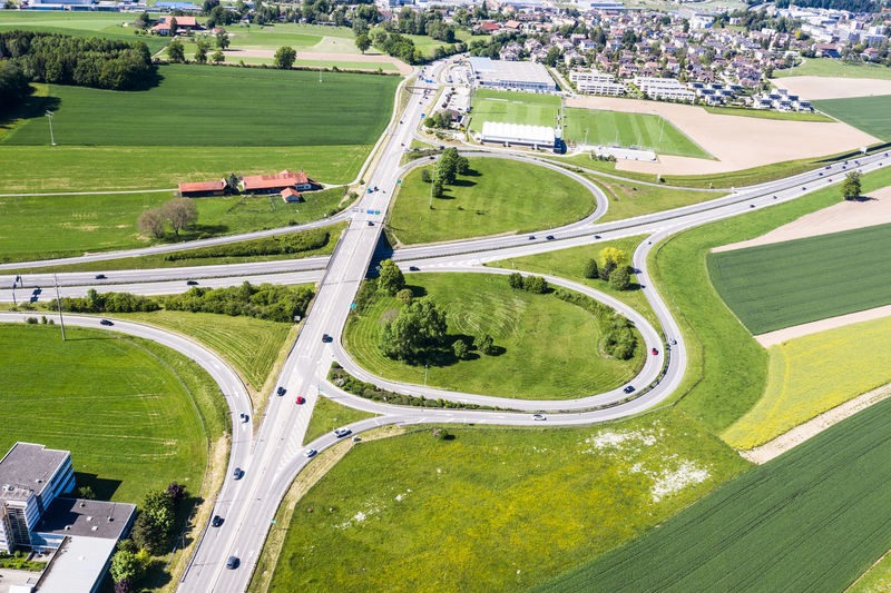 High angle view of road amidst field in city