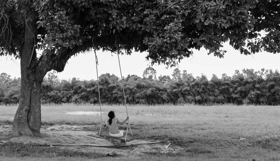 Rear view of man sitting on field