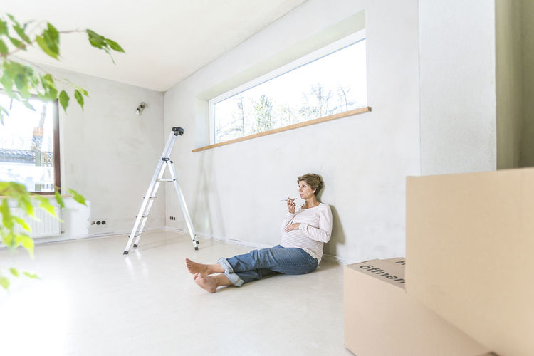 Portrait of expecting woman sitting on floor in the new house Architecture Baby Expecting Modern Mother Moving Organizing Renovation Sitting Woman Building Site Communication Empty Finance Floor House Indoors  Lifestyles Living Room Pregnancy Pregnant Relocation Screed Smartphone Young Adult