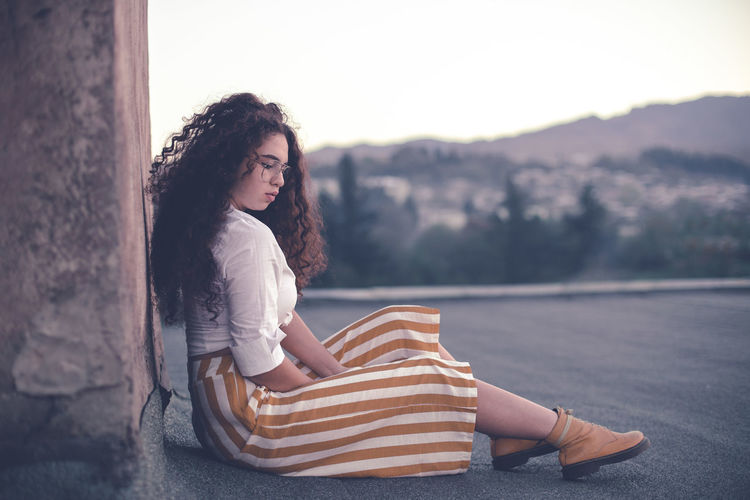 Young woman with curly hair looking away while sitting outdoors