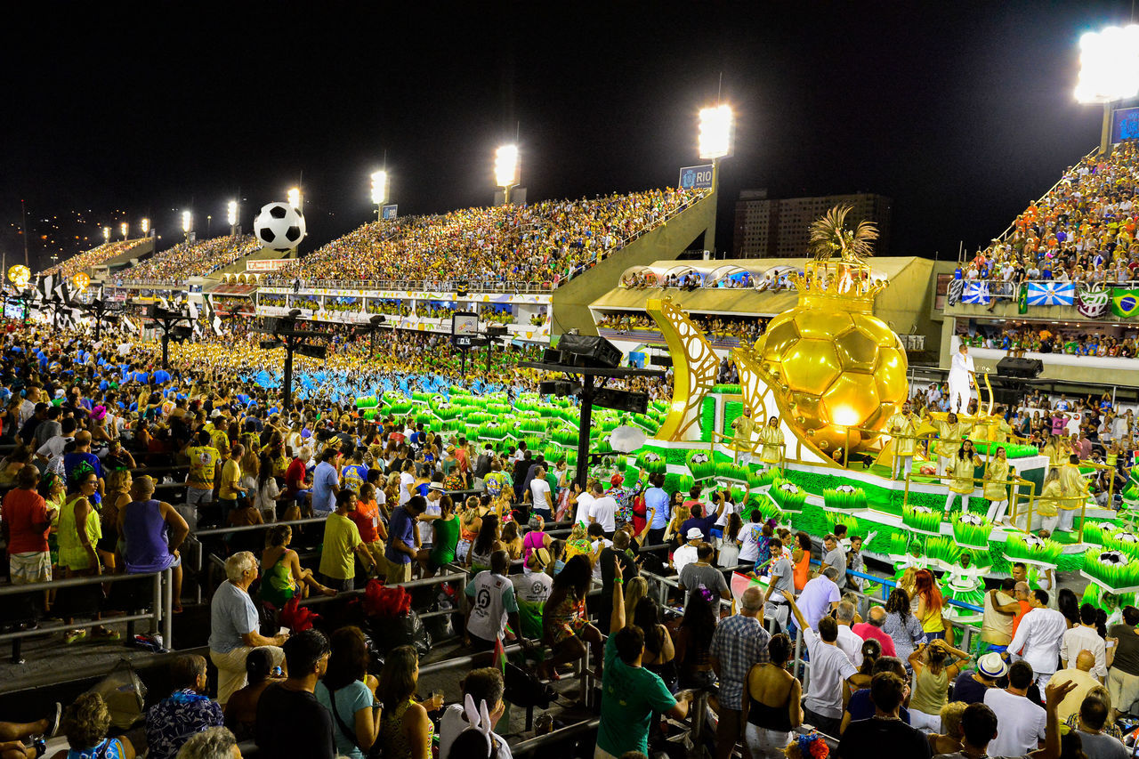 large group of people, crowd, night, real people, enjoyment, high angle view, leisure activity, men, illuminated, women, arts culture and entertainment, celebration, lifestyles, outdoors, togetherness, audience, stadium, sky, people