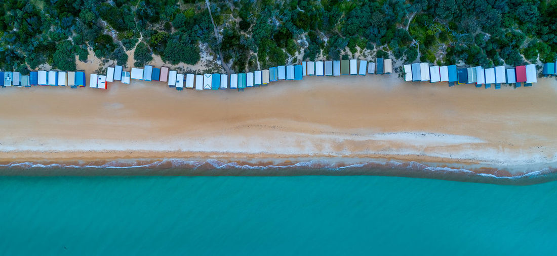 Aerial view of beach huts by sea