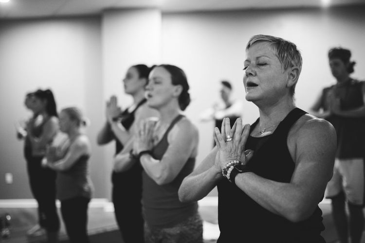 Women doing yoga while standing at studio
