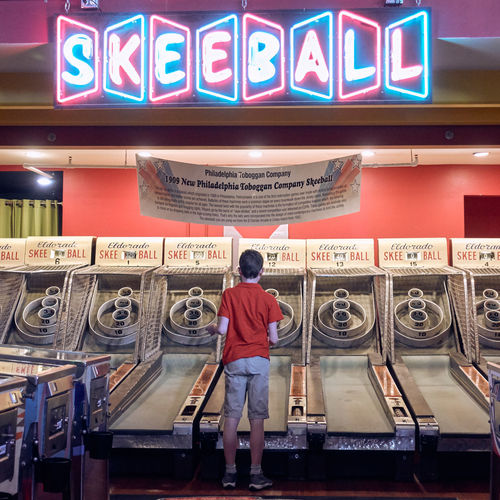 Text One Person Western Script Communication Standing Casual Clothing Illuminated Real People Full Length Indoors  Front View Machinery Arts Culture And Entertainment Occupation Adult Leisure Activity Technology Boy Skeeball Game Architecture
