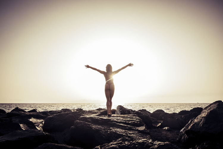 Rear View Of Woman With Arms Outstretched On Rocky Shore Against Clear Sky