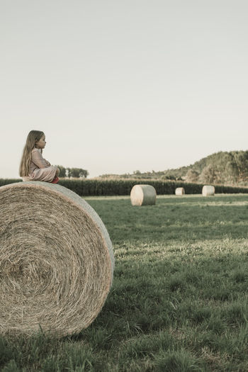 Child sitting on a hay bales on field against clear sky