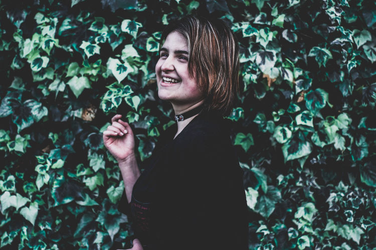 Smiling young woman standing against plants