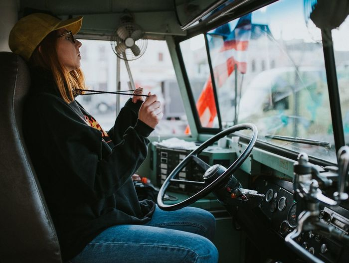 Woman sitting in truck drivers seat
