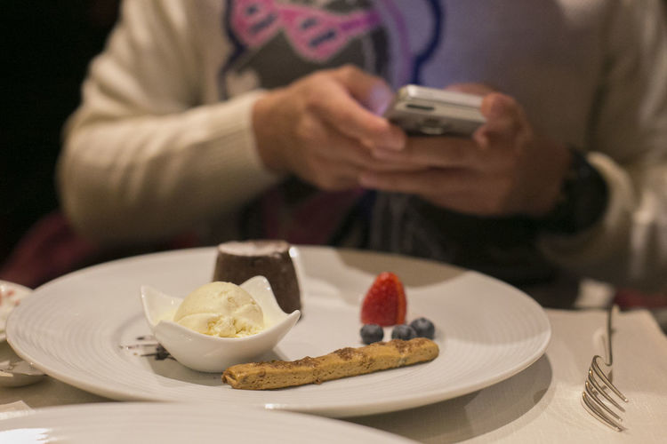 Close-up of dessert in plate against person using mobile phone