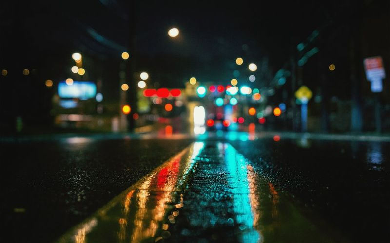 Surface level view of wet street against illuminated city