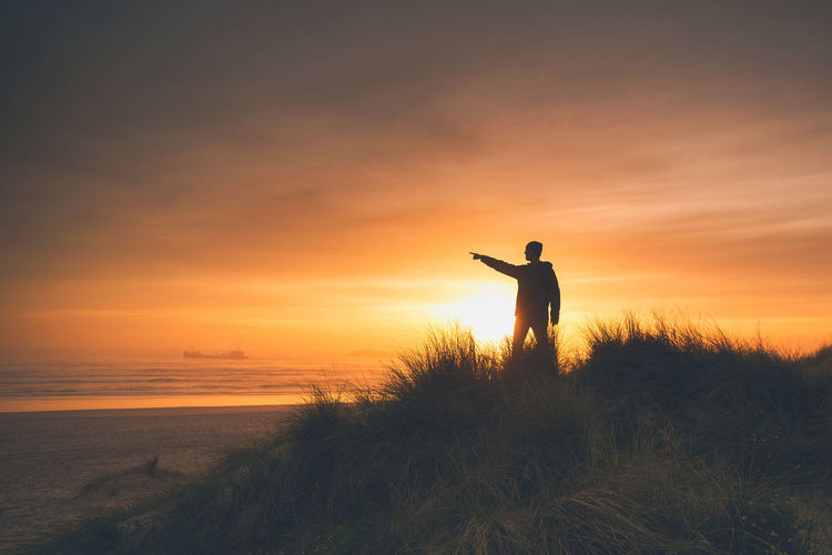 Silhouette man pointing while standing on land against sky during sunset