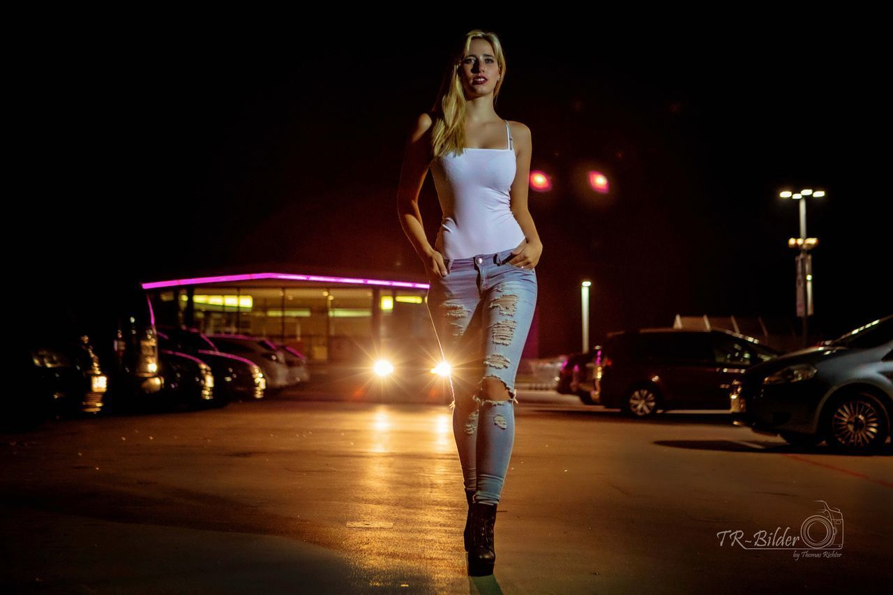 night, car, motor vehicle, illuminated, mode of transportation, transportation, young adult, one person, land vehicle, women, full length, young women, real people, standing, lifestyles, casual clothing, adult, front view, beautiful woman, hairstyle, teenager