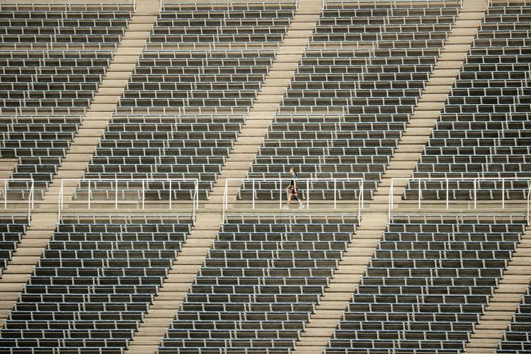 Full frame shot of empty stadium seating with one person