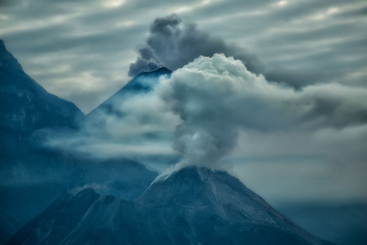 Scenic view of smoke emitting mountains against sky